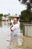 Flood waters. An older man saving his beloved dog during a flood and showing flooded items in the background Royalty Free Stock Images