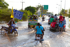 Flood waters overtake house in Thailand. AYUTTHAYA - OCTOBER 9: Pickup truck and motorcycle transporting flood victims through the streets of the city during the stock photos