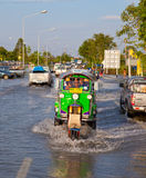 Flood waters overtake house in Thailand. AYUTTHAYA - OCTOBER 9: Pickup truck and motorcycle transporting flood victims through the streets of the city during the royalty free stock photo