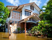 Flood waters overtake house in Thailand. AYUTTHAYA - OCTOBER 9: Women looking own house in flooded during the monsoon season of October 9, 2011 in Ayutthaya royalty free stock photo