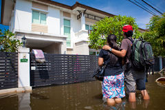 Flood waters overtake house in Thailand. BANGKOK - OCTOBER 24: The Couple looking own house in flooded during the monsoon season of October 24, 2011 in Bangkok stock images