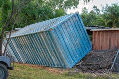 Flood Waters Pushed A Container On Its Side. A large storage container pushed onto it`s side by the force of flood waters royalty free stock image
