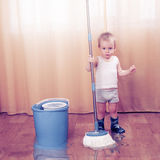 Flood. Young boy in rubber boots with mop. A lot of water on the flor Royalty Free Stock Image