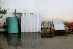 Flooded backyard junk covered with partially rusted metal barrel and grey roof tiles leaned on family house wall. On rainy spring day stock image