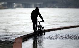 Flooded bike path after high water on a river. A biker push his cbysicleon a overflowing bicycle path beside a river Stock Images