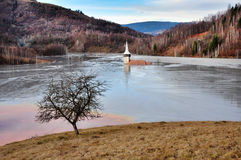 A flooded church in a toxic red lake. Water polluting by a coppe Royalty Free Stock Photo