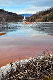 A flooded church in a toxic red lake. Water polluting by a coppe Stock Photo