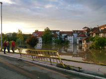 Flooded city with view of road and observers on side. Flood and disaster in town Obrenovac in Serbia, damaged houses and property, state or condition after Royalty Free Stock Image
