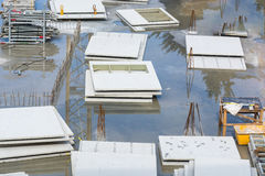 Flooded construction site with concrete walls. View of a flooded deep construction site with steel and precast concrete walls Stock Image