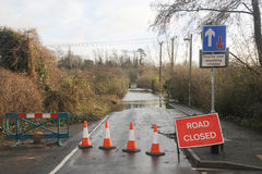 Flooded country road. A country road is closed as a swollen river breaks its banks. Hampshire, England UK Stock Image