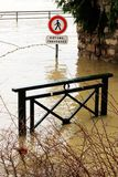 Flooded cross road warning sign Seine River banks damages Paris. Flooded cross road warning sign and the swollen Seine river. France on alert after days of heavy stock photos