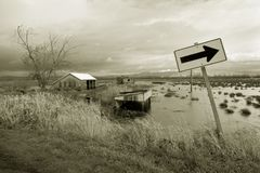 Flooded farm field and sign. Black and white view of flooded fields surrounding farm house with directional sign in foreground royalty free stock images