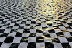 Flooded floor. Shiny, reflective, black and white checkered surface with waves and reflections of a sunset environment. Resembling a flooded floor Royalty Free Stock Images