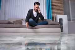 Man Sitting On Sofa Calling To Plumber. Flooded Floor From Water Leakage In Front Of Man Sitting On Sofa Calling To Plumber royalty free stock photos