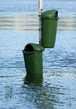 Flooded garbage containers. River water flooding two garbage containers Royalty Free Stock Image