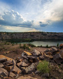 Flooded granite quarry. The shot of old flooded granite quarry on the back of dramatic sky Stock Photos