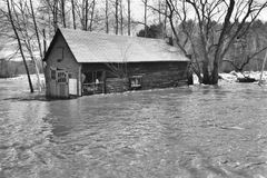 Flooded house. Old barn during a flood,shown in black and white Stock Photo