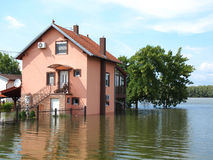 Flooded house. Big flooded house with blue sky and white clouds in high water stock photo