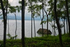 Flooded house in Lake Batur. In the forest behind the trees stock photo