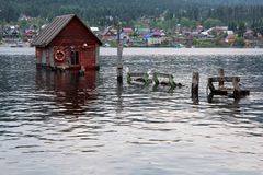 Flooded house on the pier. Water after the flood flooded part of the buildings on the shore stock images