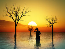 Flooded land. Desperate woman standing in a flood plain watching the sunrise Royalty Free Stock Photography