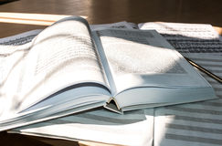 Flooded with light:  open book, sheet music and music notebook. Stock Image