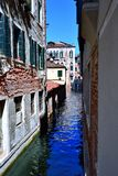 Flooded narrow street in Venice. Blue water of the canal in Venice Italy royalty free stock photography