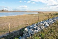 Flooded part of a Dutch polder. With in front a fence of wooden poles and wire as well as rock chunks diagonally in the picture Stock Image