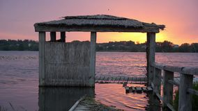 Flooded pier on the shore of the lake. Flooded wooden pier / bungalow on the shore of the lake stock footage