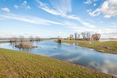 Flooded polder in the end of the winter season. Flooded polder on a sunny day in the end of the winter season. In the background a farmer`s barn with an orange Stock Photography