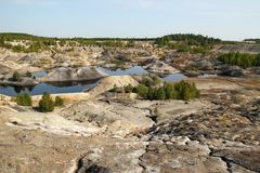 Flooded quarry with lakes and dried hills with rare vegetation. Royalty Free Stock Images