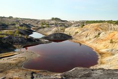 Flooded quarry with red water and dried hills with rare vegetation. Stock Photo