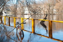 Flooded river in the city. Fishing poles relied on bicycle in flooded river Royalty Free Stock Photography