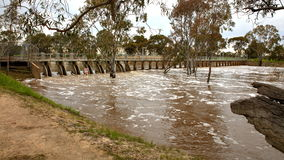 Flooded river over weir. Flood waters passing over weir on the Wimmera River in Horsham, Victoria, Australia Royalty Free Stock Photos