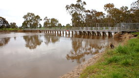 Flooded river over weir. Flood waters passing over weir on the Wimmera River in Horsham, Victoria, Australia Stock Images