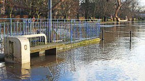 A Flooded Riverside. Riverside seats covered in floodwater Stock Photo