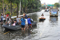 Flooded Road. City residents navigate a flooded street by boats and trucks as tens of thousands of Bangkokians evacuate their homes in the worst flooding in over Stock Photos