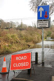 Flooded road closed. A country road is closed as a swollen river breaks its banks. Hampshire, England UK Stock Photo