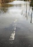 Flooded road. A country road is closed as a swollen river breaks its banks. Hampshire, England UK Stock Photos