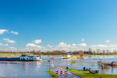 Flooded road in front of the Dutch river IJssel Royalty Free Stock Images
