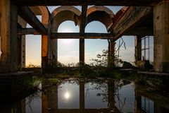 Flooded ruined abandoned building with arches. Reflection of sky and moon in water royalty free stock photo