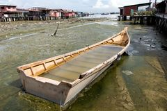 Flooded ship in mud at village on pillars. Malaysia. Flooded ship in mud at village on pillars. Abandoned boat at Clan Jetties of George Town, Penang, Malaysia stock photos