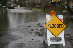 Flooded sign sits on a flooded street stock images