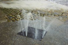 Flooded Street. Flood water flowing out of a manhole onto the street Royalty Free Stock Photography