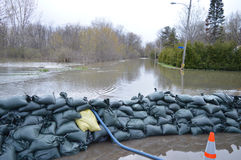 A street near Ottawa, flooded with houses being protected by a wall of sand bags. Sand bags protect a neighbourhood after Spring flooding in Gatineau near royalty free stock photo