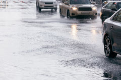 Flooded street road with car traffic driving on it after rain Royalty Free Stock Photo