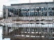 Flooded  territory of abandoned ruined industrial factory building with broken facade and windows, reflection in water stock photography