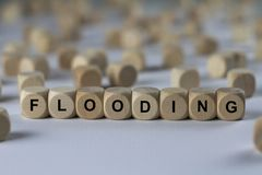 Flooding - cube with letters, sign with wooden cubes royalty free stock images