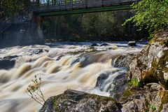 Flooding river streaming fast. In spring time. Walking bridge going over river stock photo