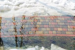 Flooding of tile walkpath due to snow melting and rising of water level. Blue sky in puddle reflection.Spring emergency incident. High water or fresget Stock Photos